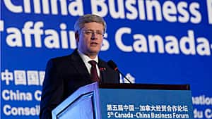 Prime Minister Stephen Harper speaks to a business group in Beijing during his 2012 trip to three Chinese cities. Business leaders and government officials defend the Harper government's decision to pay the tab for executives in his delegation as a good investment.