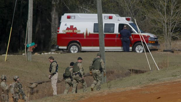 Law enforcement officials, including the FBI, at the scene of a shooting and hostage taking near Midland City, Alabama.