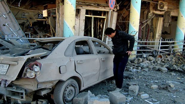 A man inspects a destroyed car at the scene of Saturday's attack in Kirkuk.