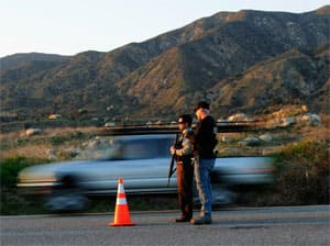 Armed police set up road blocks to stop traffic kilometres away from the cabin where a suspect believed to be Christopher Dorner was holed up.