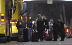 Passengers load their belongings onto buses after docking at the cruise terminal in Mobile, Ala.
