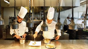 Two chefs prepare a dish in a high-end restaurant. There are signs that U.S. diners are staying home lately.