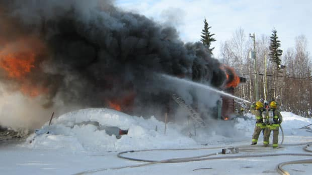 Hay River, N.W.T., firefighters at the scene of a fire that destroyed a home on Vale Island Monday.