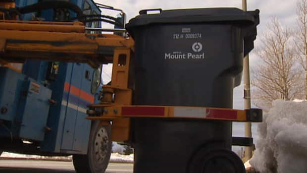 A robotic arm prepares to pick up a garbage bin in Mount Pearl.