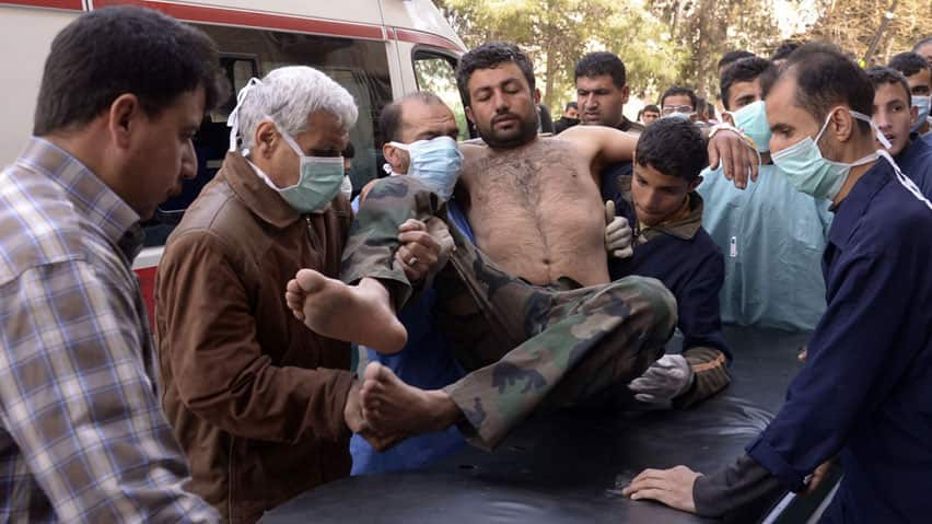 Medics move a Syrian Army soldier wounded in what government officials are calling a chemical weapon attack near Aleppo.