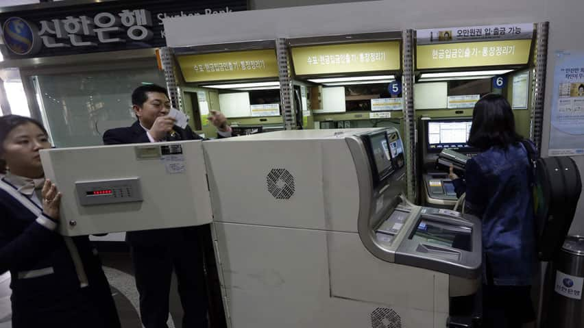 Two bank clerks, left, check an automated teller machine at a branch of Shinhan Bank after the bank's computer networks are fixed in Seoul, South Korea. Computers networks at two major South Korean banks and three top TV broadcasters went into shutdown mode en masse Wednesday, paralyzing bank machines across the country and prompting speculation of a cyberattack by North Korea.