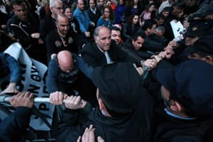 Employees of Laiki bank push barriers as riot police try to stop them during an anti-bailout protest outside the Cypriot parliament.