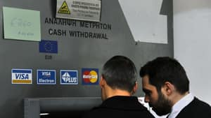 A sign in the upper left informs depositors that they can withdraw a maximum €260, as people queue up to make transactions at an ATM of Laiki Bank in Nicosia, Cyprus on Friday.