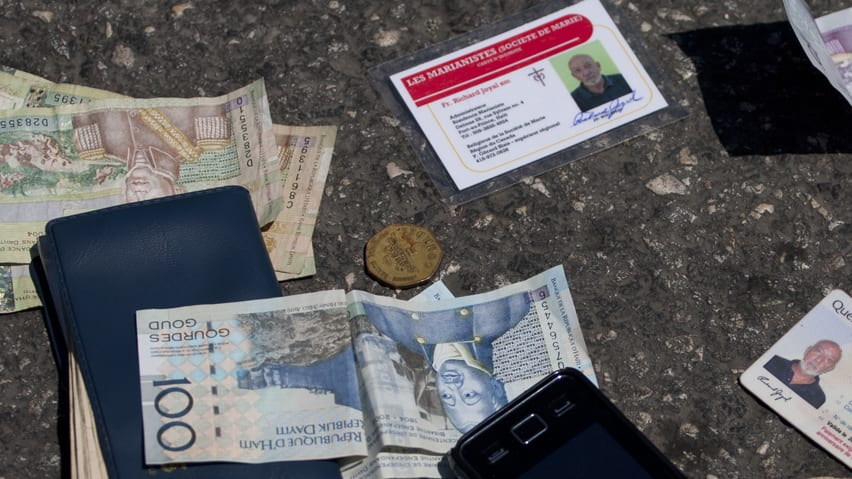 Identification cards, cash, a phone, a key and an item with a bank logo lay on the street after being placed there by authorities next to the body of Canadian priest Richard E. Joyal, , after he was killed Thursday in Delmas, a district of Port-au-Prince, Haiti.
