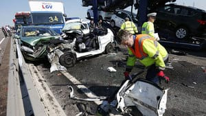 A rescue worker works amid the wreckage of some of the 100 vehicles involved in multiple collisions, which took place in dense fog during the Thursday morning rush hour on the Sheppey Bridge in Kent, east of London.