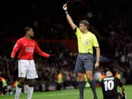 Manchester United's Patrice Evra, left, is given a yellow card Tuesday by referee Roberto Rosetti for a foul on Lyon's Karim Benzema, right, during their match at Old Trafford Stadium, Manchester, England.