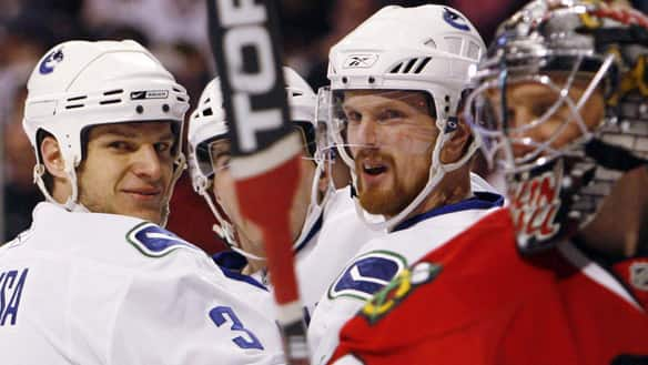 Vancouver's Daniel Sedin, right, and Kevin Bieksa will be looking to get to Blackhawks goalie Nikolai Khabibulin.