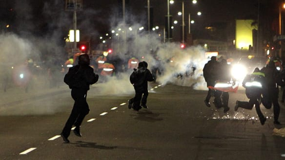 Protestors flee police officers firing tear gas canisters and rubber bullets