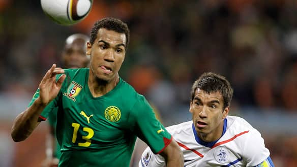 Cameroon's Eric Choupo-Moting, left, and Netherlands' Giovanni van Bronckhorst chase the ball during the Group E finale for both teams in Cape Town, South Africa.