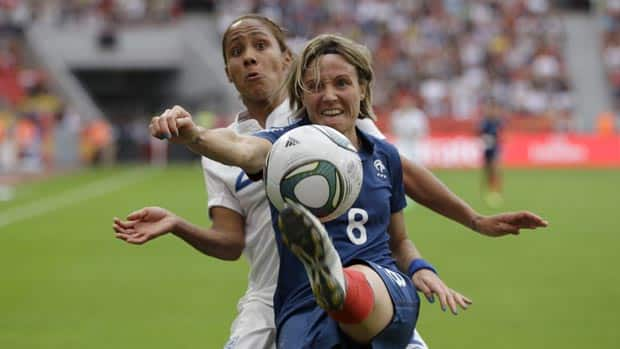 France's Sonia Bompastor and England's Alex Scott, back, challenge for the ball during Saturday's match.