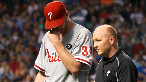 Philadelphia Phillies' Roy Halladay, left, leaves the game with trainer Scott Sheridan during the fifth inning of a game against the Chicago Cubs on Monday in Chicago.