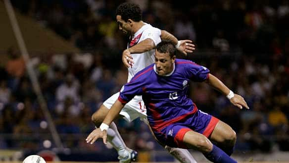Canada's Dwayne De Rosario, back, dribbles past Puerto Rico's John Krause, front, during a 2014 World Cup qualifying soccer game in Bayamon, Puerto Rico, Tuesday. Canada won 3-0.