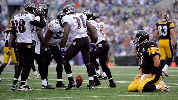 Members of the Baltimore Ravens celebrate Ed Reed's interception of a pass by Pittsburgh Steelers quarterback Ben Roethlisberger, kneeling at foreground right.