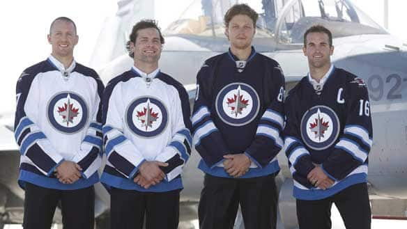 Eric Fehr, far left, was on hand to help the Jets unveil their new sweaters, but he won't be able to suit up for a game until at least November.