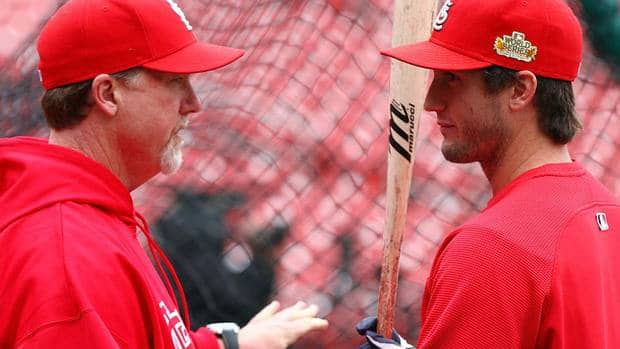 Former major league slugger-turned Cardinals hitting coach Mark McGwire, left, talks with David Freese during batting practice.