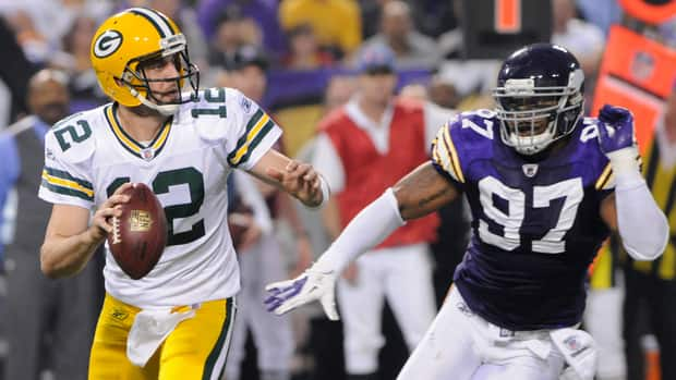 Green Bay Packers quarterback Aaron Rodgers (12) runs from Minnesota Vikings defensive end Everson Griffen, right, during the second half on Sunday in Minneapolis.