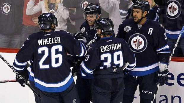 Winnipeg's Blake Wheeler (26), Andrew Ladd (16) and Tobias Enstrom (39) celebrate Ladd's first-period goal against the Washington Capitals on Friday night.