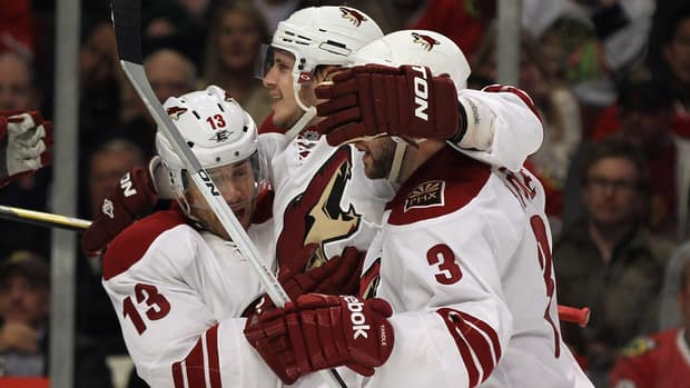 Ray Whitney, left, and Keith Yandle, right, of the Phoenix Coyotes hug teammate Oliver Ekman-Larsson after Larsson scored a second period goal against the Chicago Blackhawks.