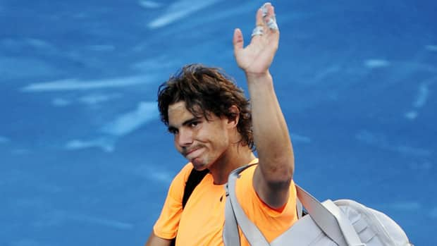 Defending French Open champion Rafael Nadal waves to supporters after losing his match to compatriot Fernando Verdasco at the Madrid Open Thursday.