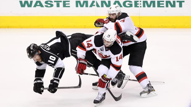Mike Richards (10) of the Kings is checked off the puck by Adam Henrique (14) and Andy Greene of the Devils on June 6.