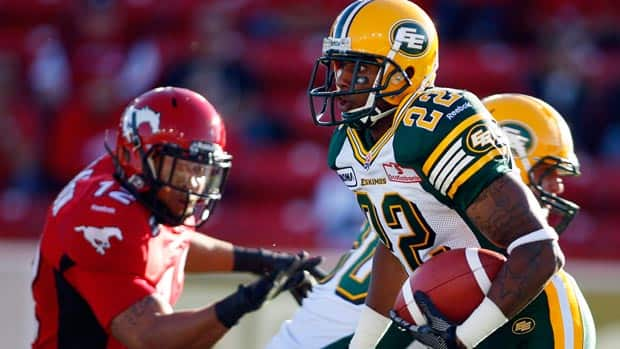 Edmonton Eskimos' Joe Burnett, centre, runs the ball during first half CFL pre-season football action against the Stampeders in Calgary.