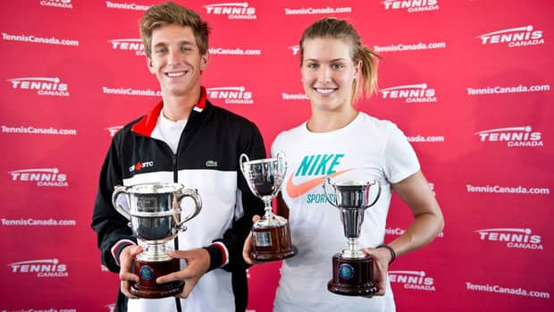 Canadian tennis players Eugenie Bouchard and Filip Peliwo pose for a photograph with their trophies in Montreal after winning junior Grand Slam titles at Wimbledon.