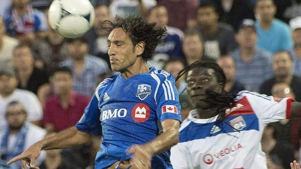 Olympique Lyonnais' Bafetimbi Gomis looks on as Montreal Impact's Alessandro Nesta heads the ball clear.