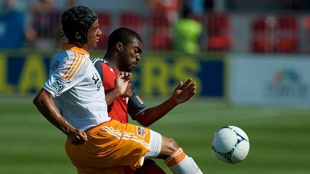 Houston Dynamos Calen Carr, left, battles Ashtone Morgan of Toronto FC on Saturday. TFC's hot run came to an end with a 2-0 defeat.
