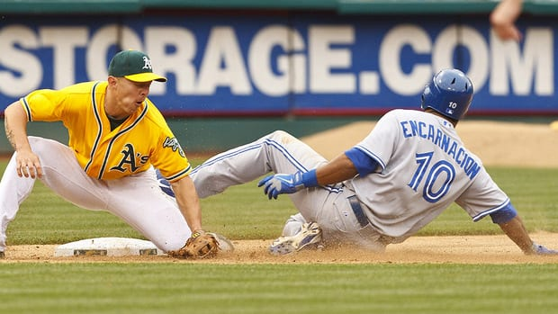 Blue Jays' Edwin Encarnacion steals third base in front of Athletics third baseman Brandon Inge in the 11th inning. Encarnacion scored on the play on Oakland catcher George Kottaras's error.