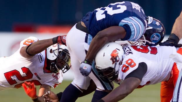 Argos running back Andre Durie (centre) is tackled by the B.C. Lions Anthony Reddick, left, and Jabar Westerman during the first half on Monday in Toronto.