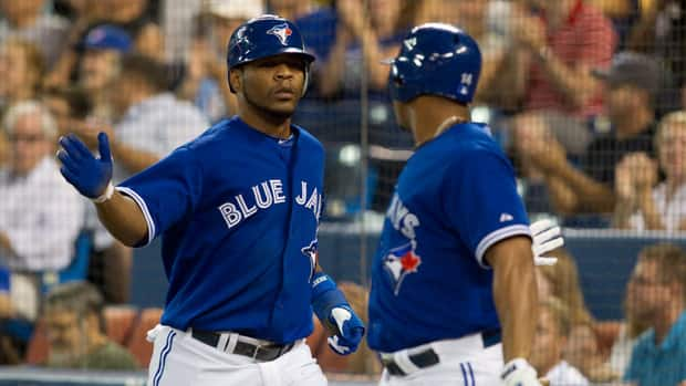 Toronto Blue Jays' Edwin Encarnacion, left, celebrates with Moises Sierra after scoring in the first inning against the Yankees on Sunday, August 12, 2012.