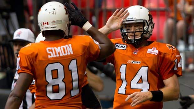 B.C. Lions' quarterback Travis Lulay, right, and Geroy Simon celebrate after Lulay rushed for a touchdown in the first half.