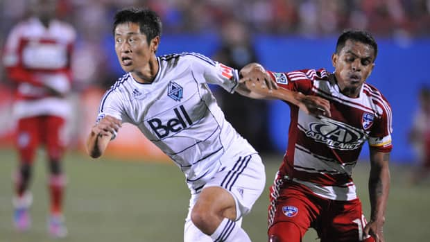 Lee Young-Pyo of the Vancouver Whitecaps, left, battles for the ball against David Ferreira of FC Dallas on September 15, 2012.