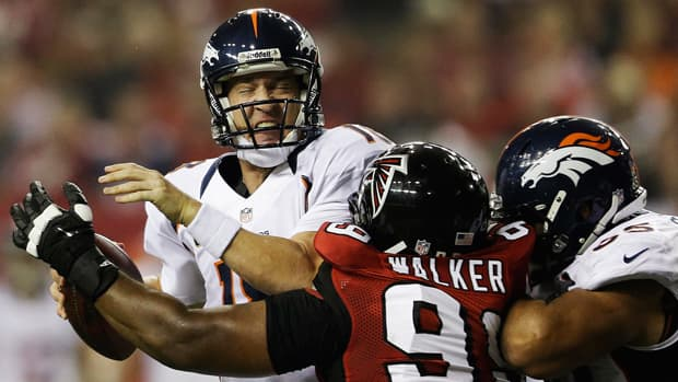 Atlanta Falcons defensive tackle Vance Walker sacks Denver Broncos quarterback Peyton Manning as guard Manny Ramirez attempts to block during the first half of Monday's game in Georgia.