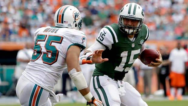 New York Jets quarterback Tim Tebow carries the ball as Miami Dolphins outside linebacker Koa Misi pursues during Week 3 action.