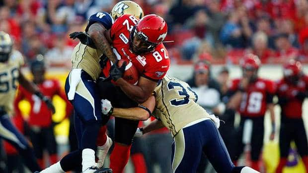 Winnipeg Blue Bombers' Johnny Sears, left, and Ian Logan, right, try to bring down Calgary Stampeders' Nik Lewis during their game last month.