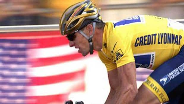 In this July 25, 2004 file photo, overall leader Lance Armstrong, of Austin, Texas, rides down the Champs Elysees avenue past U.S. flags during the 20th and last stage of the Tour de France cycling race.