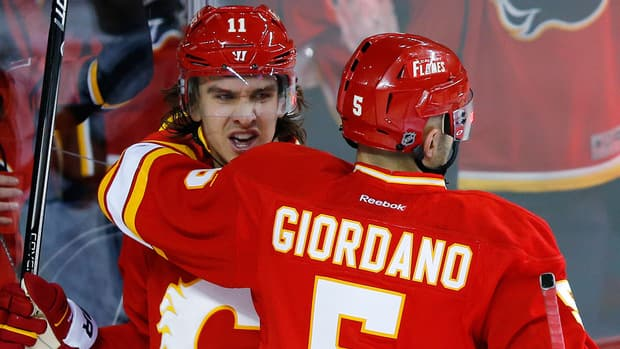 Calgary Flames' Mikael Backlund, left, celebrates his goal with teammate Mark Giordano during the first period Saturday against the Edmonton Oilers.