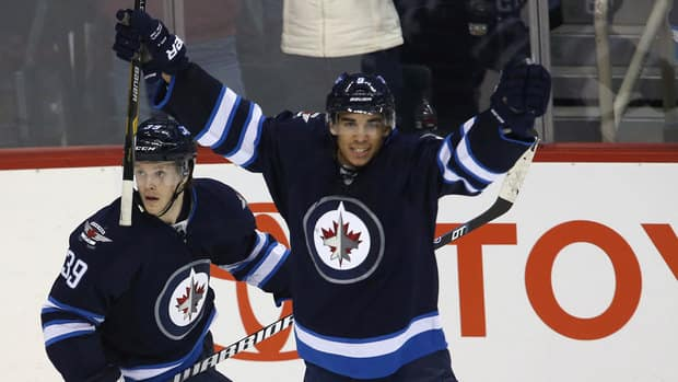 Winnipeg Jets' Evander Kane, right, celebrates after scoring the game-winning goal in overtime Sunday against the New York Islanders.