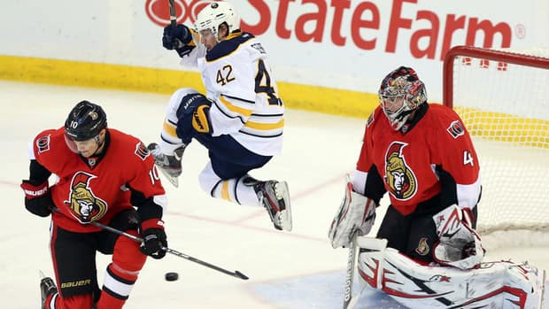 Buffalo Sabres forward Nathan Gerbe (42) jumps as he screens a shot on Ottawa Senators goaltender Craig Anderson (41) as Senators' Mike Lundin (10) looks on during the first period on Tuesday night.