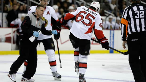 Senators defenceman Erik Karlsson, right, limps off the ice after suffering an Achilles injury in Pittsburgh.