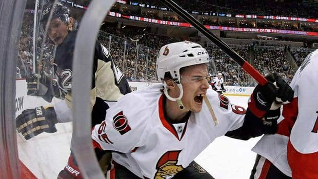 Ottawa Senators defenceman Erik Karlsson (65) grimaces as he falls to the ice after colliding with Pittsburgh Penguins left wing Matt Cooke, left, on Wednesday. Karlsson may be out for the season as a result.