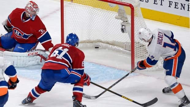 Montreal Canadiens goaltender Carey Price, left, is scored on by New York Islanders defenceman Thomas Hickey, right, as Canadiens' Raphael Diaz defends during overtime on Thursday night in Montreal.