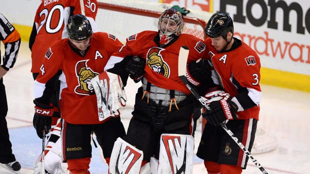 Ottawa Senators goalie Craig Anderson, centre, is helped off the ice in the third period against the New York Rangers.