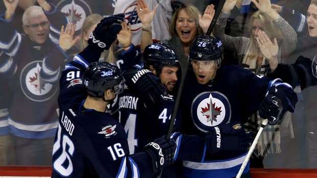 Winnipeg Jets' Andrew Ladd, left, Zach Bogosian, centre, and Blake Wheeler celebrate Wheeler's goal against the Boston Bruins.